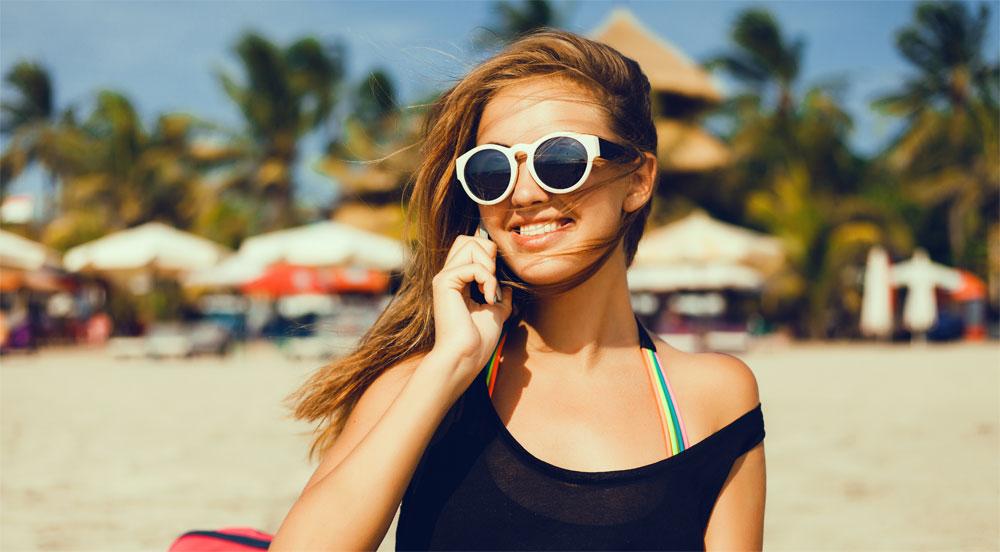 Am Strand telefonierende Frau